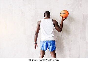 Calm athletic guy playing with ball - Relaxed african...