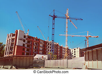 cranes under a blue sky - many tall buildings under...