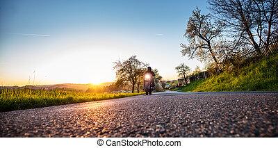 Dark motorbiker riding high power motorbike in sunset - Dark...
