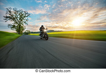 Dark motorbiker riding high power motorbike in sunset - Dark...