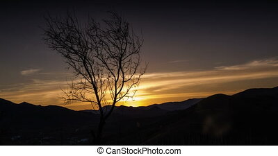 The sun sets over the mountains and passes through the...