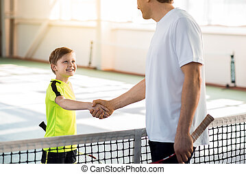 Proud tennis couch praising his pupil - Good game. Trainer...