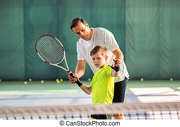 Skillful trainer teaching kid holding racquet - Professional...