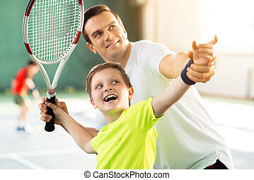 Happy child playing sport game with his parent - Excited boy...