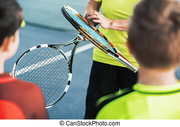 Trainer showing sports equipment to kids - Close up of hand...
