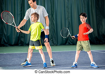 Concentrated tennis player teaching kids on court - Serious...