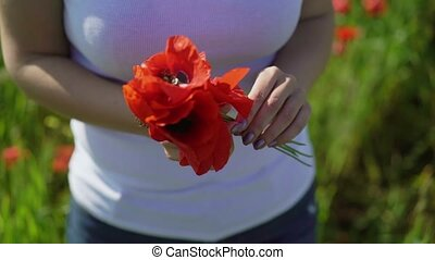 Young woman in poppy field with flowers