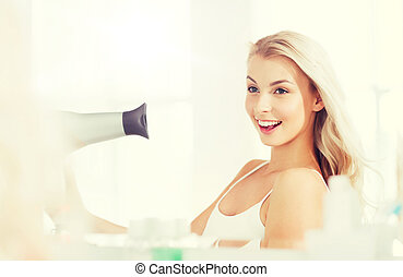 happy young woman with fan drying hair at bathroom - beauty,...