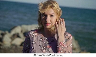 Young blonde woman in dress near sea at windy day