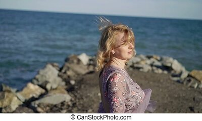 Young blonde woman in dress near sea circling