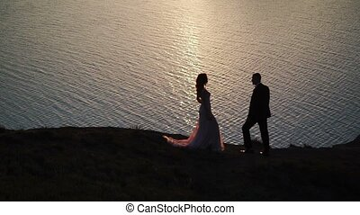Young couple holding hands on sunset near sea