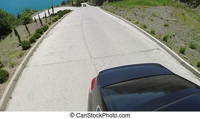 Car driving on mountain road at sunny day