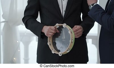 Man in suite with tambourine closeup