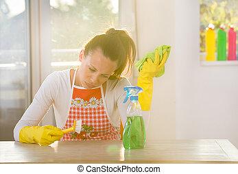 Woman scrubbing desk - Tired woman with apron scrubbing...