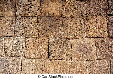 a wall made of irregular yellow volcano stone cubes - angkor wat
