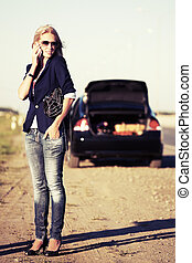 Young fashion woman with broken car calling on the cell...