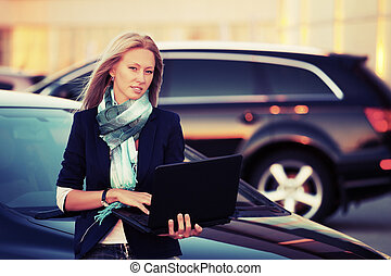 Young fashion business woman with laptop by car