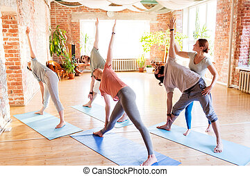 group of people doing yoga exercises at studio - fitness,...