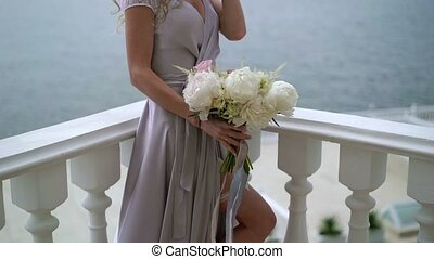 Young woman staying with bouquet on balcony