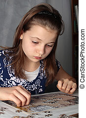 Teenage girl 12-13 years old doing puzzle on table