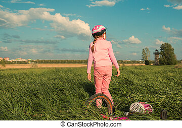 A girl of seven in a pink helmet walks in the evening on the grass, next to her bicycle