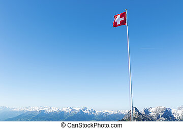 Waving Swiss flag in front of blue sky and mountain range