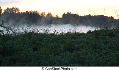 Fog and rising sun on river, idyllic landscape. Video for...