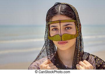 Girl in mask bandari woman, beach of Persian Gulf, Iran. -...