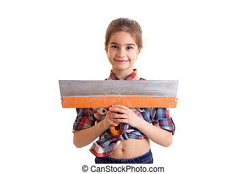 Little girl holding putty knife - Little positive girl with...