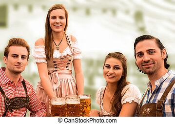 Waitress delivers beers in tent with happy visitors in a...