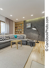 Spacious grey living room with comfortable sofa and small...
