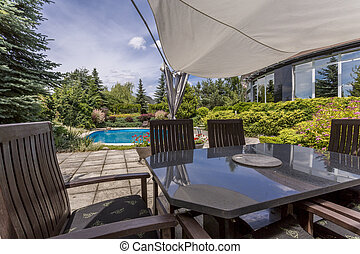 Outdoor furniture set and swiming pool - Image of a stylish...