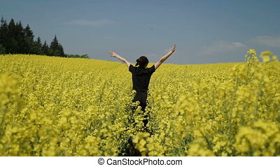Young Woman in Black clothes overalls Running through Yellow Field Touching Flowers HD