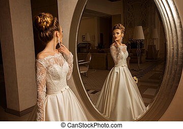blonde bride in wedding dress looking at the mirror - Sexy...