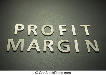 Profit margin written with wooden letters on a yellow background