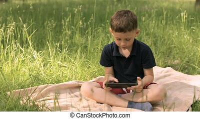 Boy with tablet in park on a meadow