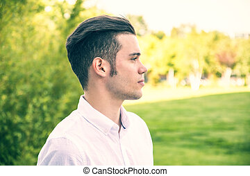 Attractive young man in city park