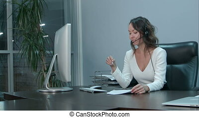 Young beautiful asian businesswoman with headset in office....