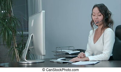 Friendly young asian female operator working on laptop with headset at modern office