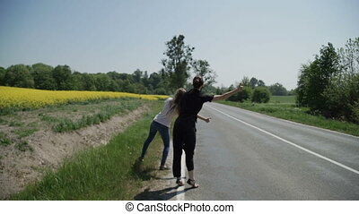 Two young women hitchhikers stand on the sidelines and ask to stop the passing cars