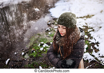 Girl in snowfall in the park near the river