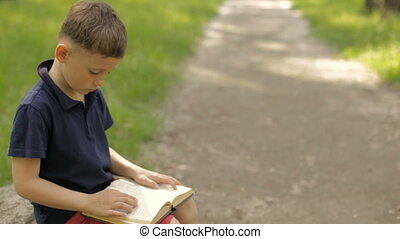 A boy with a book in the park on the mall