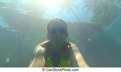 happy girl happy swims underwater in the pool. Sunlight through the water