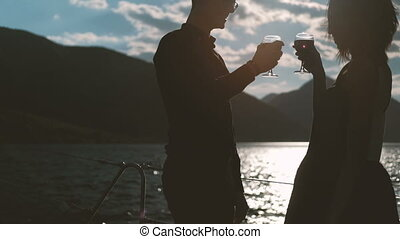 Young couple drinking wine standing on beach on summer day....