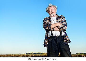old farmer in the field - An elderly farmer standing in a...