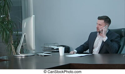 Young caucasian businessman calling with smartphone and talking seriously in office