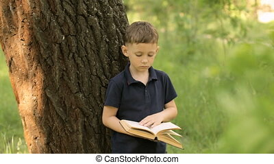 A boy is reading a book standing near a tree
