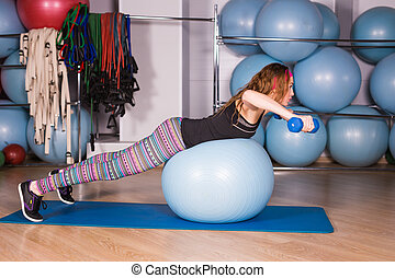 Young sporty woman in gym doing fitness exercice with blue...