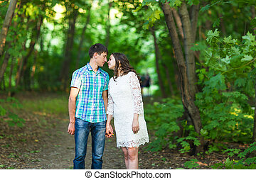 Portrait of a young romantic couple kissing each other on nature