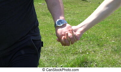 Couple in love walking on a green field and holding hands.